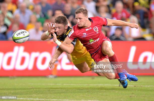 Beauden Barrett of the Hurricanes and James Tuttle of the Reds challenge for the ball during the Super Rugby round six match between the Reds and the...