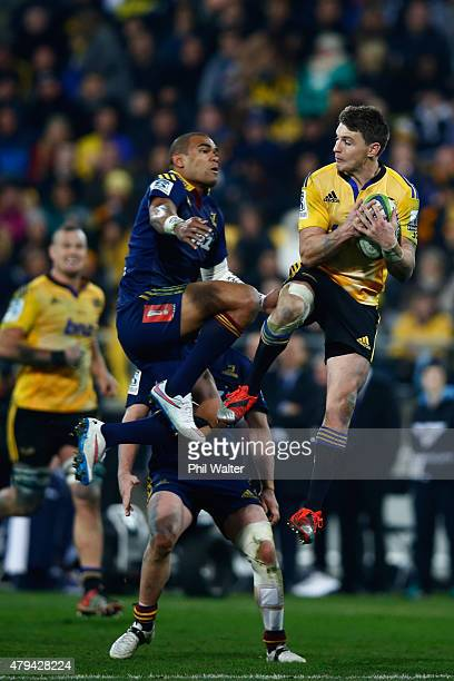 Beauden Barrett of the Hurricanes collects the high ball over the top of Patrick Osborne of the Highlanders during the Super Rugby Final match...
