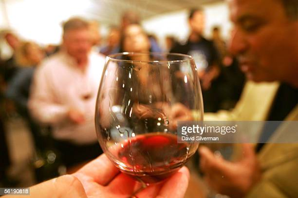 Beaujolais Nouveau 2005 is swirled in a glass during a celebration for the young wine in a wine shop moments after midnight November 17 2005 in...