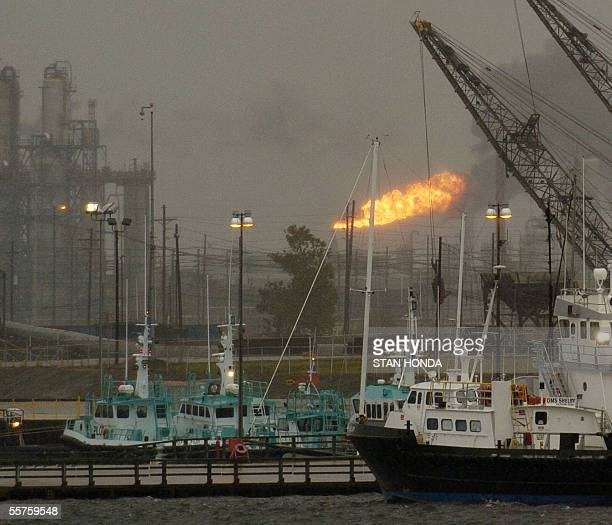 As a flame from an oil refinery is blown sideways boats sit docked in the Beaumont Texas harbor on Friday 23 September 2005 as Hurricane Rita...
