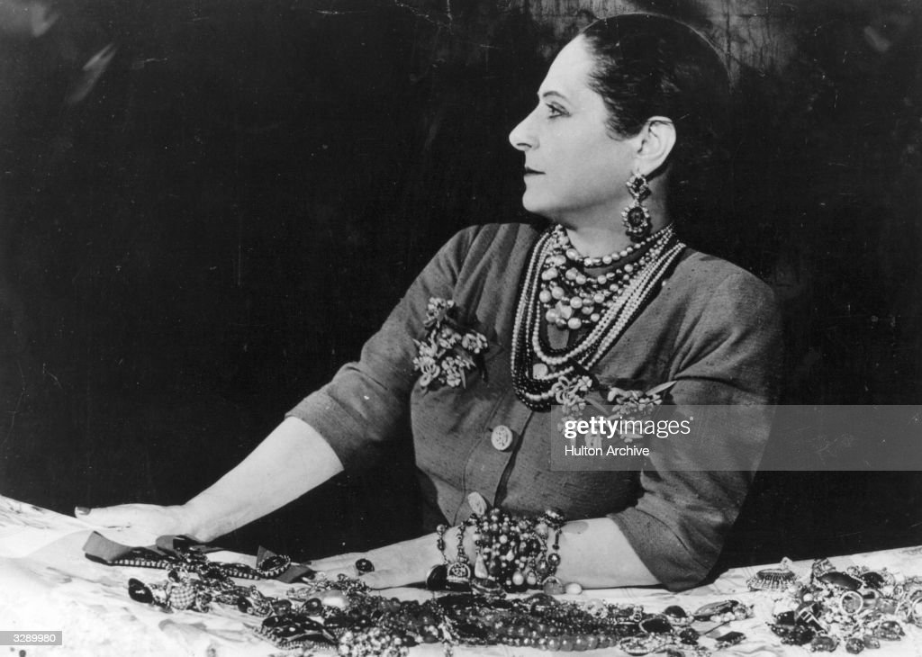 Beautician and business executive Helena Rubinstein modelling a selection of jewellery.