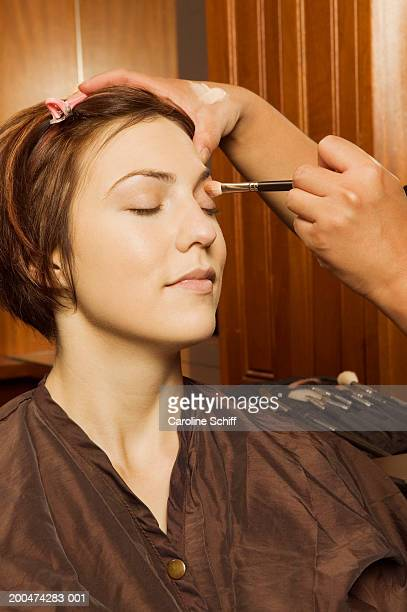Beautician applying make-up to young woman's eyes in spa
