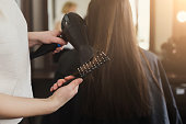 Beautician drying woman's hair after giving a new haircut at salon. Beauty, care, hair cocnept