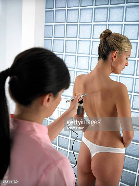 Beautician giving spray tan to woman, rear view