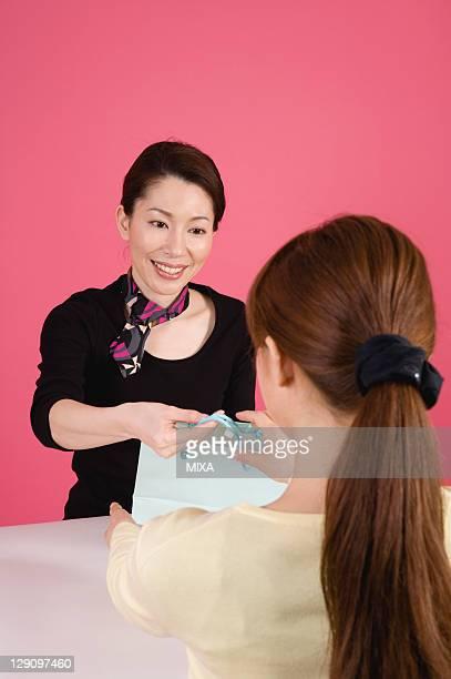 Beautician Handing Paper Bag to Customer