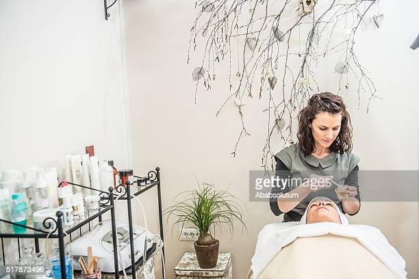 Beautician Putting Oil on Pretty Wpoman's Face, Beauty Salon, Europe