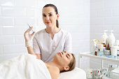 Beautician with syringe with filler for facial contouring or augmentation. Doctor doing beauty procedure for patient. Cosmetological clinic. Healthcare, cosmetology. Hyaluronic acid, scincare concept