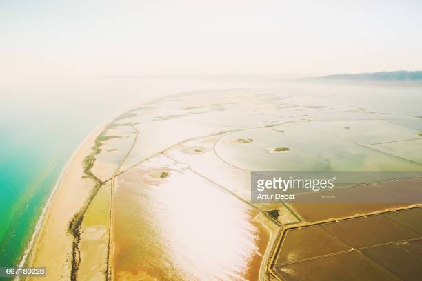 Beautiful aerial picture flying over Delta del Ebro, a unique nature outdoor with beautiful colors and textures, with beach and colorful salt pans in the Catalonia region.