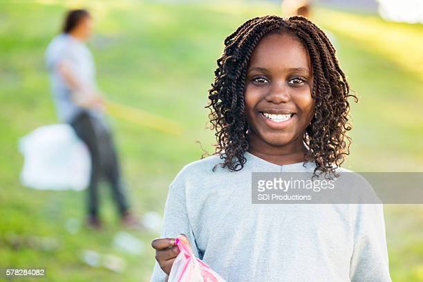 Beautiful African American girl participates in neighborhood cleanup