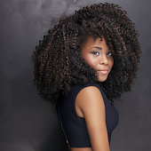 Young beautiful african american girl posing in elegant dress, looking at camera. Girl with afro. Studio shot. Black background.