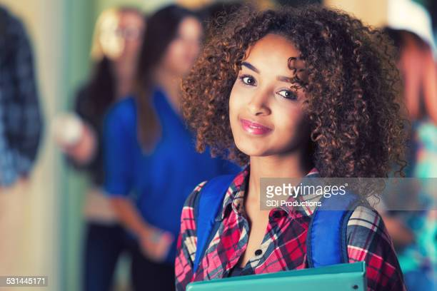 Beautiful African American girl standing in school hallway