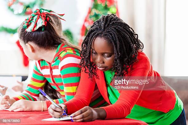 Beautiful African American girl writes in Christmas card
