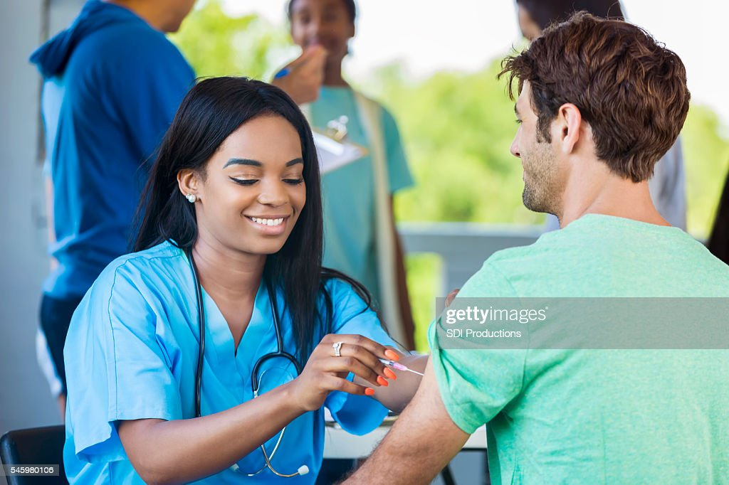 Beautiful African American Nurse administering a vaccination