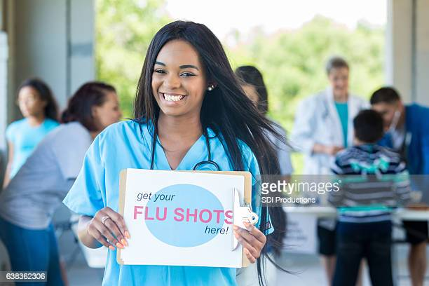 Beautiful African American nurse promotes flu shots at health fair
