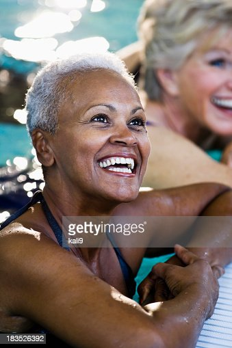 Beautiful African American senior woman in swimming pool laughin
