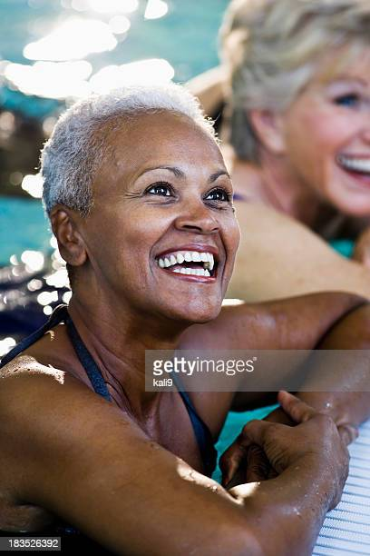 Beautiful African American senior woman in swimming pool laughin