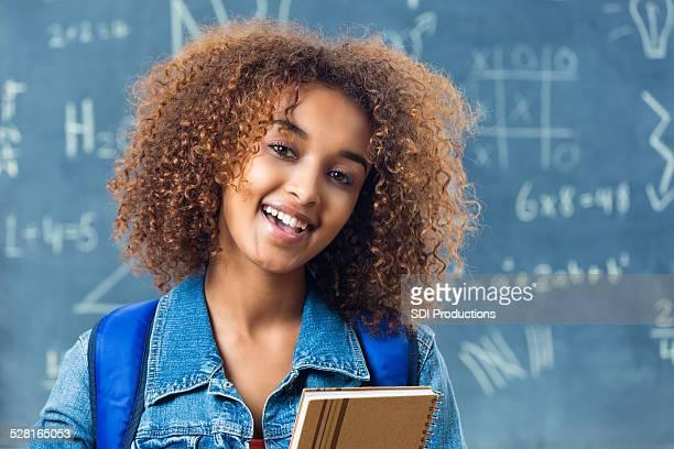 Beautiful African American teen girl standing in front of blackboard