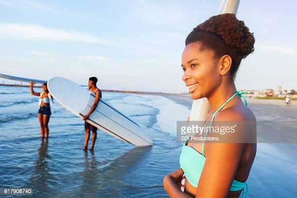 Beautiful African American teenage girl with surfboard