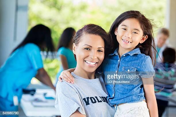 Beautiful African American volunteer holding an adorable little girl