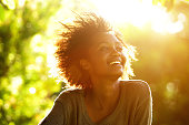 Close up portrait of a beautiful african american woman smiling with sunset