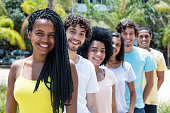 Beautiful african american woman with dreadlocks with multi ethnic friends in line outdoor in the summer