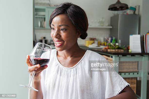 Beautiful african female smiling with wine in her hand.