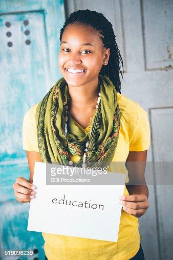Beautiful African teenage girl holding 'education' sign