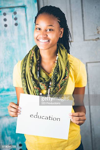 Beautiful African teenage girl holding 'education' sign