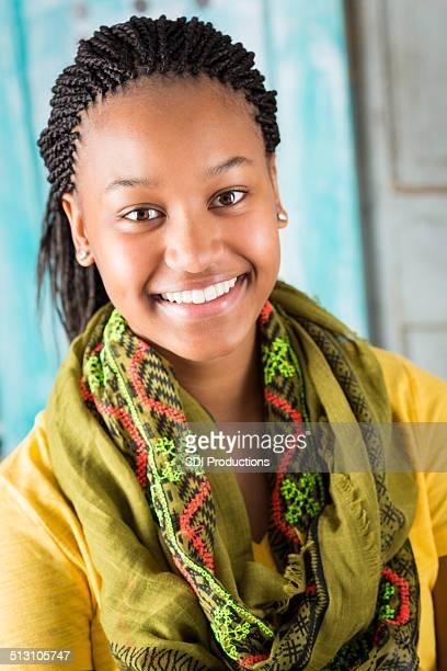 Beautiful African teenager smiling at camera outdoors