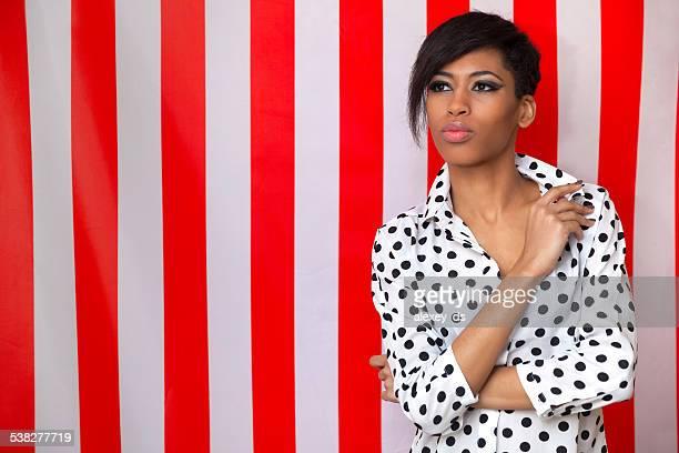 Linda mulher Africana em polka dot camisa em fundo listrado