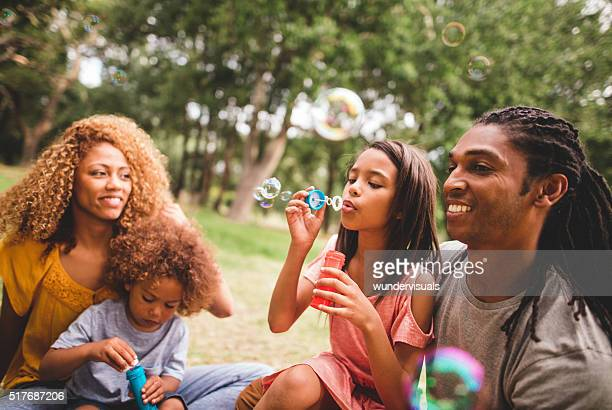 Beautiful african-american family having a picnic and blowing bu