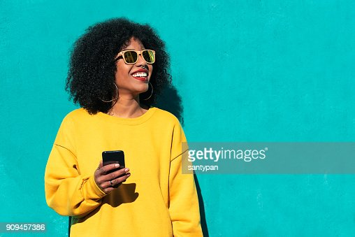 Beautiful afro american woman using mobile in the street. : Stock Photo