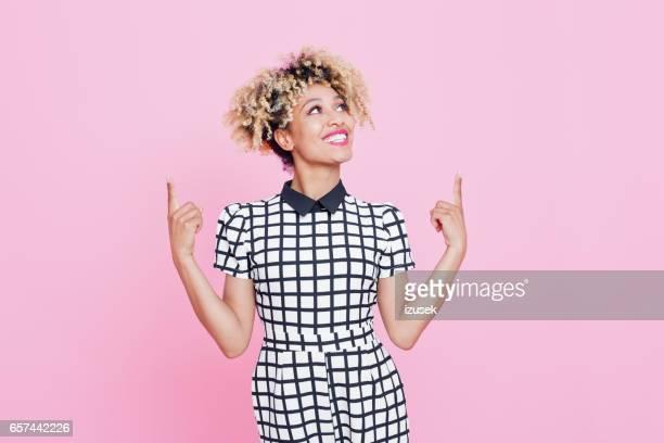 Schöne Afro amerikanische junge Frau zeigte auf Textfreiraum