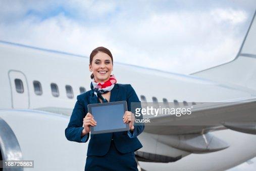Beautiful air stewardess with a digital tablet