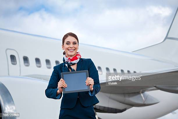 Beautiful air stewardess with a digital tablet