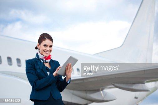 Beautiful air stewardess with digital tablet