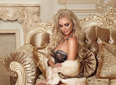 Beautiful alluring blond woman in sexy lingerie and fur coat posing on royal sofa with pillows in luxurious modern interior. Beauty glamour fashion style photo portrait.