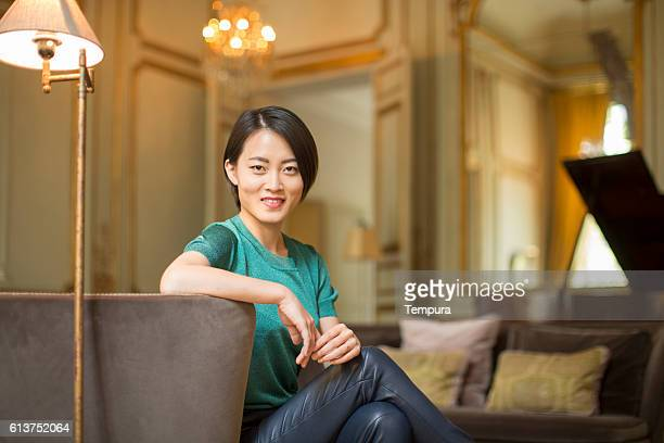 Beautiful and elegant woman sitting in a luxury livingroom