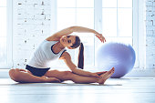 Young beautiful young woman in sportswear doing stretching while sitting in front of window at gym