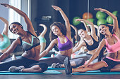 Young beautiful young women with perfect bodies in sportswear doing stretching with smile at gym