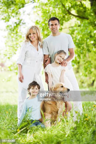 Beautiful and happy family with their dog in a park.