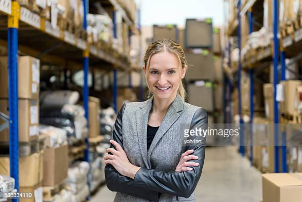 Beautiful and happy female boss in warehouse