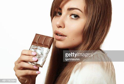 Beautiful And Lovely Girl Eating Chocolate Stock Photo Thinkstock