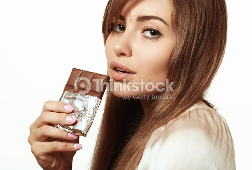 Beautiful And Lovely Girl Eating Chocolate Stock Photo Thinkstock