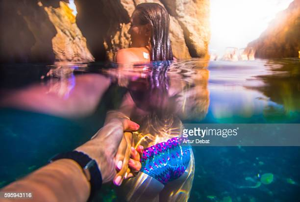 Beautiful and sensual girl lead the way holding hands of a guy taken the picture from personal point of view with underwater view in the Costa Brava during summer vacations. Follow me.