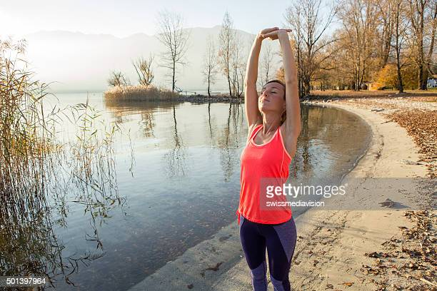 Beautiful and sporty young woman stretching after jogging outdoors