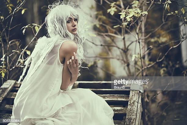 Schöne Engel in einem weißen Kleid im Freien.