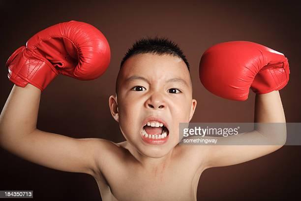 Magnifique en colère jeune garçon joue avec des gants de boxe
