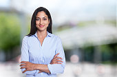 Beautiful arabic businesswoman with crossed arms outdoor in front of an office building