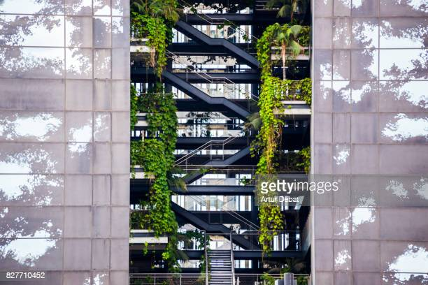Beautiful architecture building with levels and vegetation growing inside of the building.